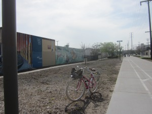 Murals line the bikeway to the right. This would be a great place for cafes, coffees shops and bakeries.